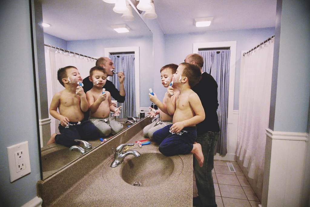 Dad and two sons shaving