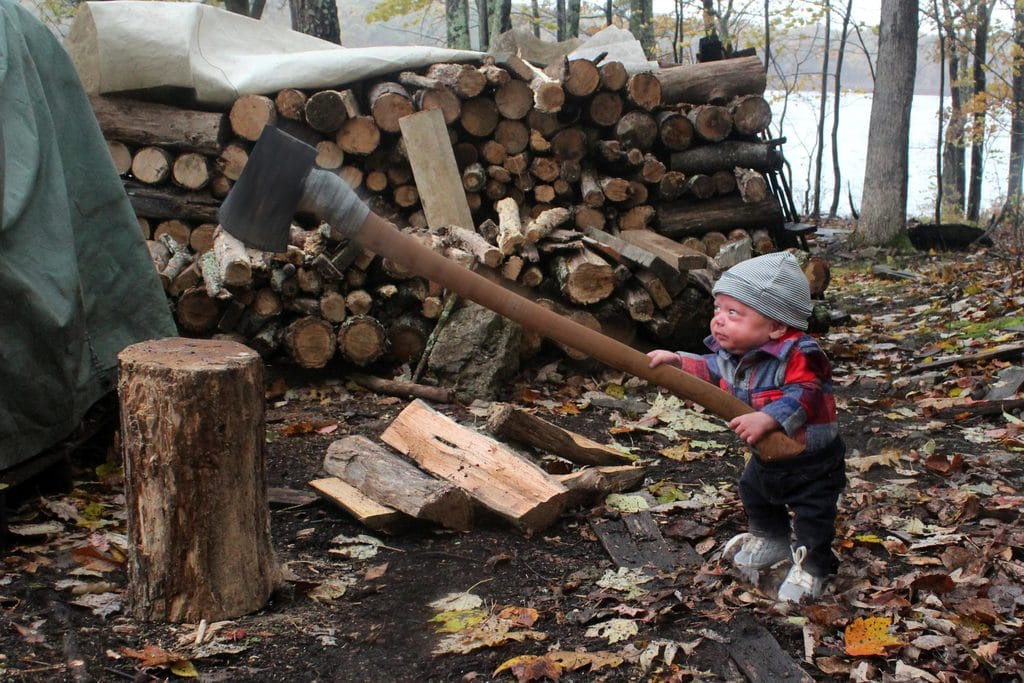A photo of baby with an ax