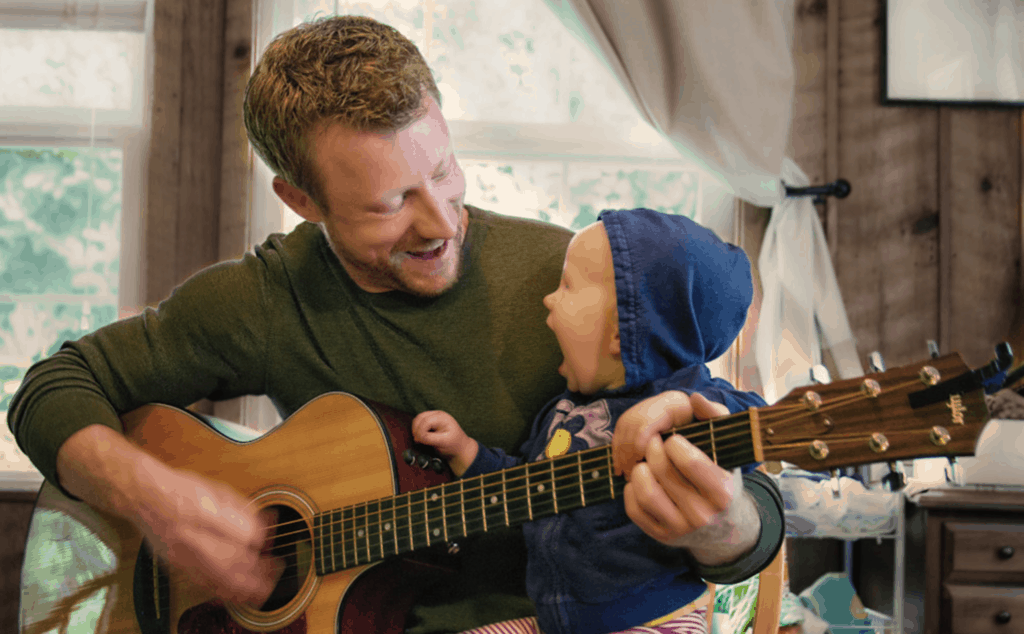 Dad playing the guitar to his baby