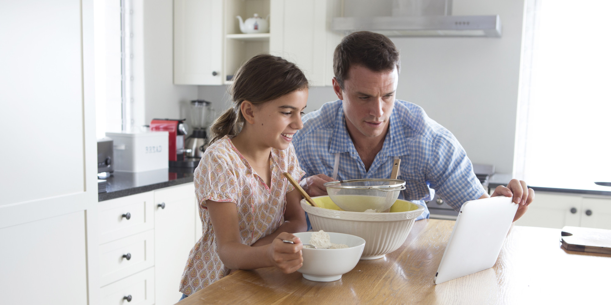 Father and daughter cooking in their kitchen