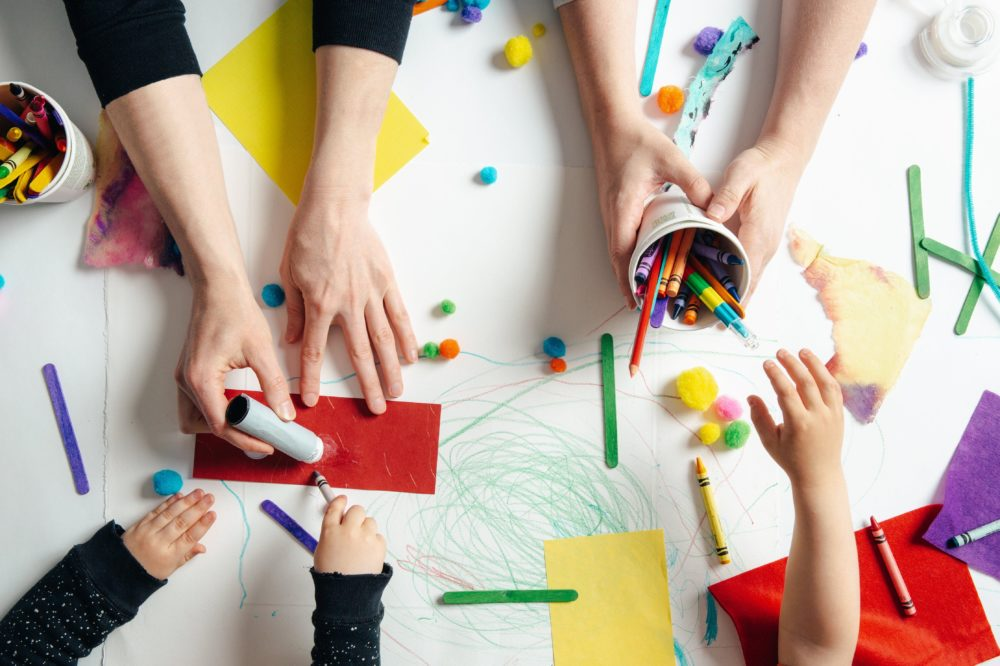 Kids and adults with art supplies