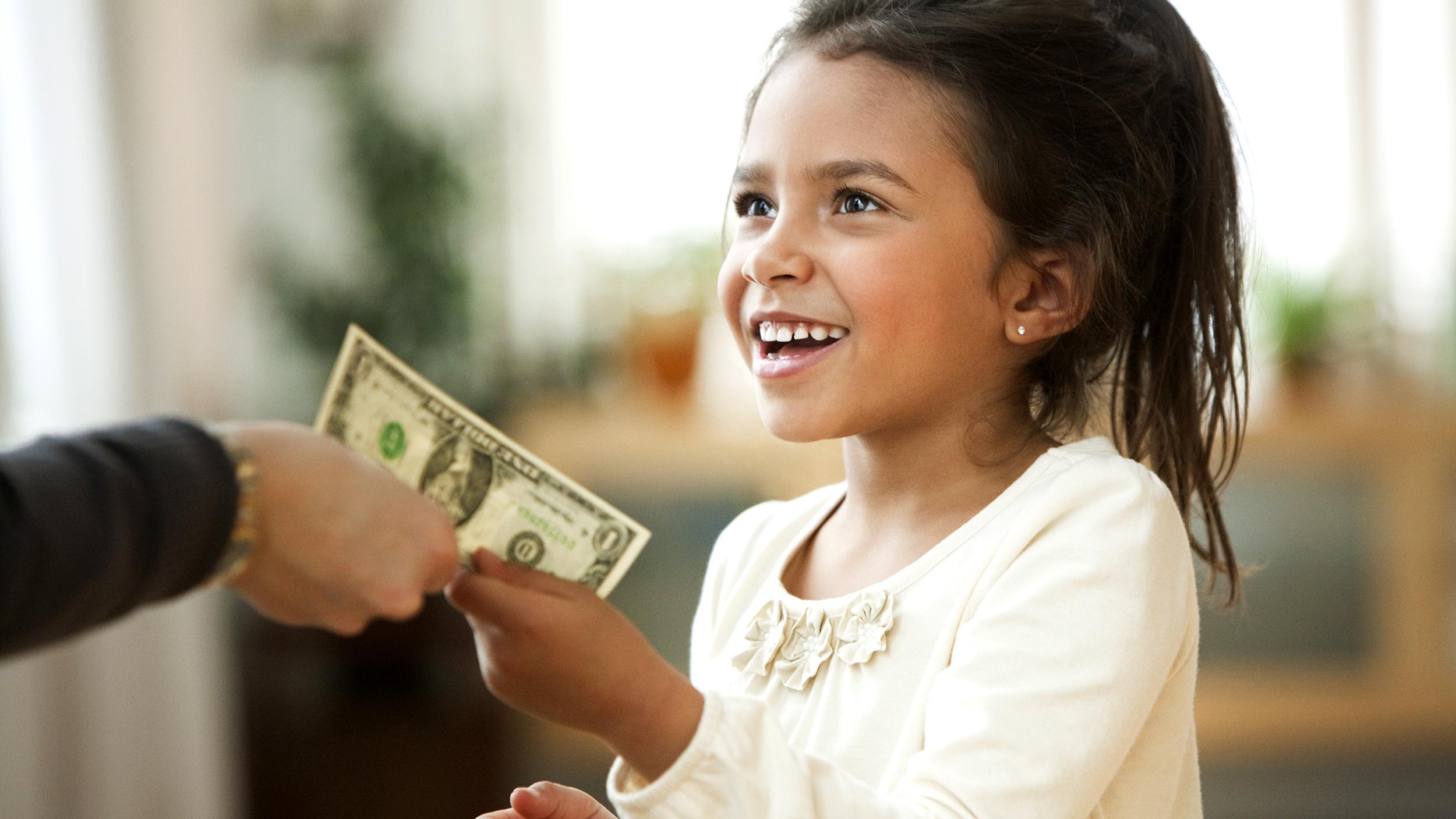 Parent handing girl one dollar bill