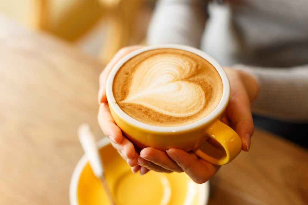 Holding a yellow cup of coffee with heart-shaped foam on top