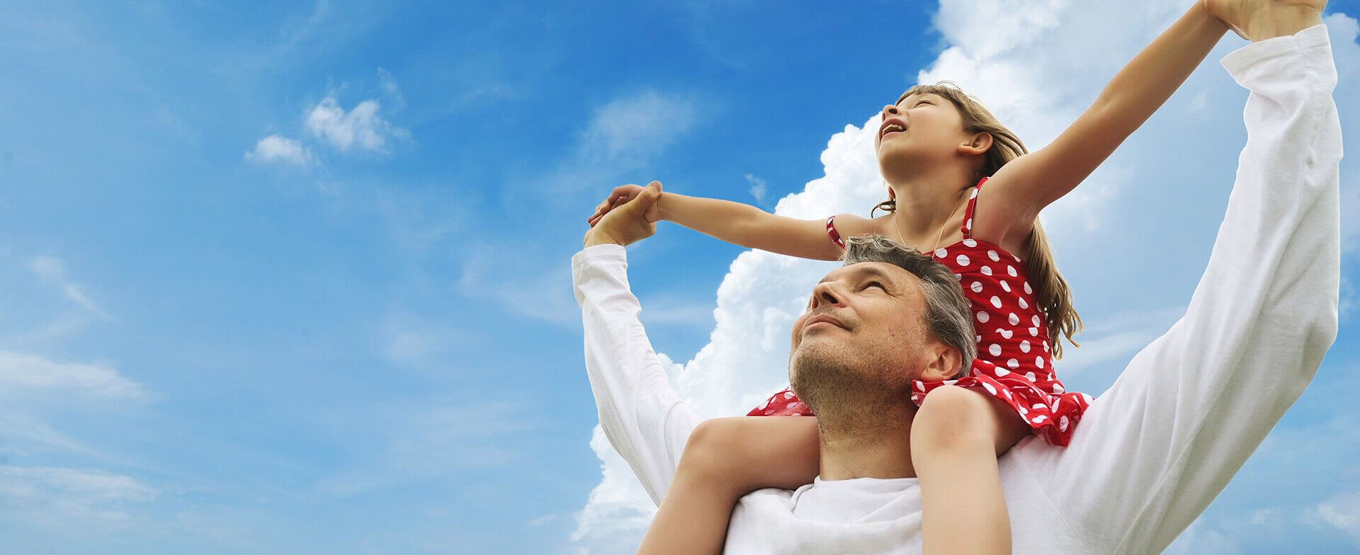 Dad lifting his daughter on his shoulders and looking up to the sky