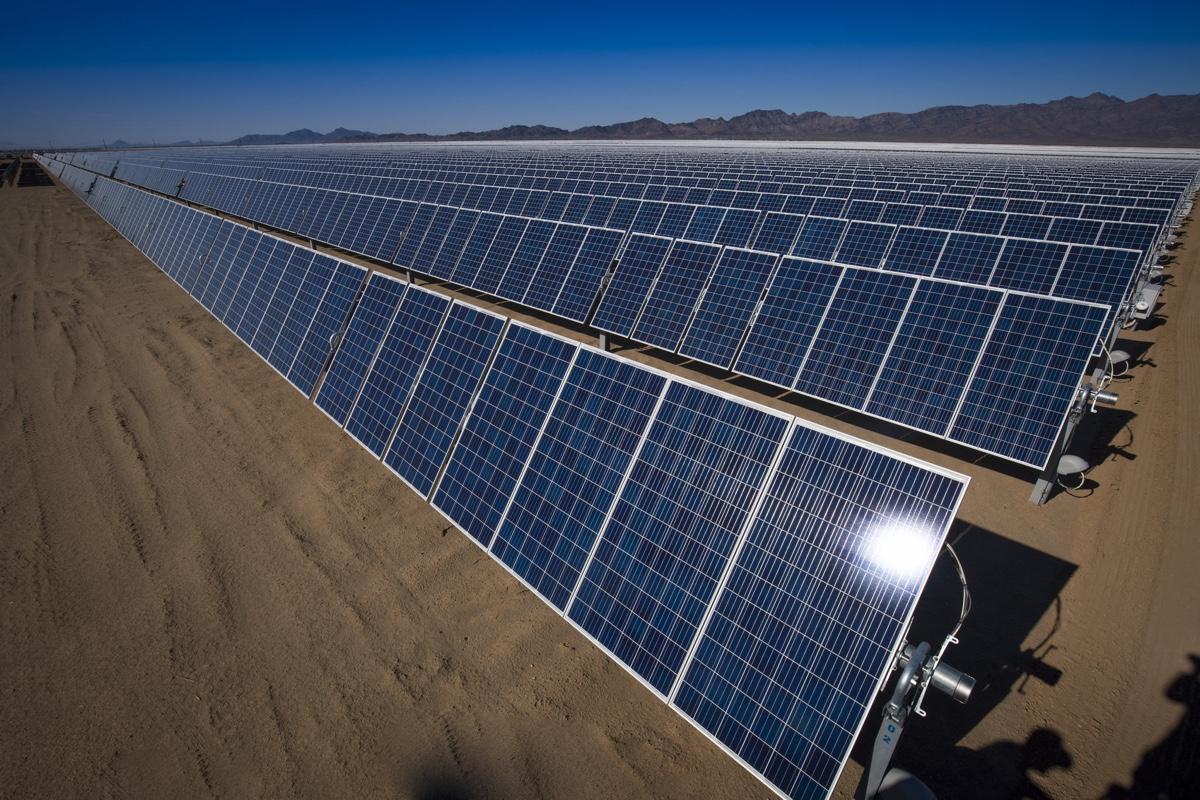A long line of solar panels on a sandy soil