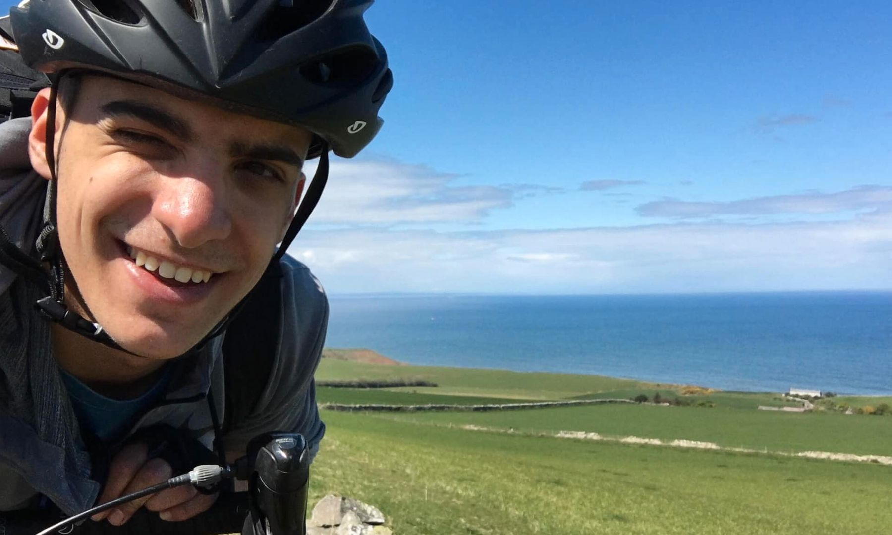 Kleon taking a selfie while on his bike with pastures and sea behind him
