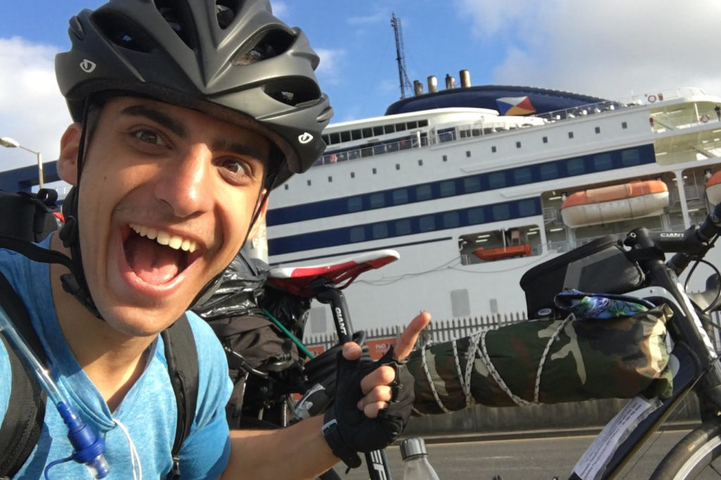 Kleon taking a selfie next to a giant boat on a port
