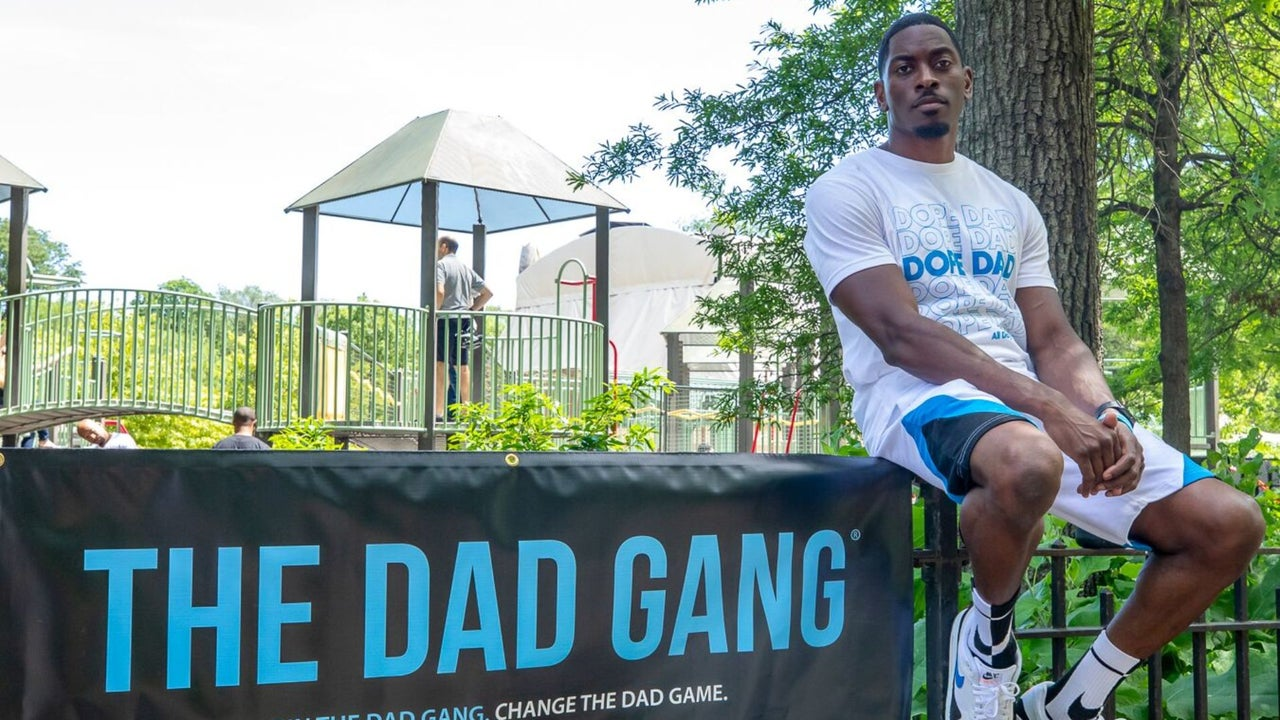 The founder of the Dad Gang next to a branded poster