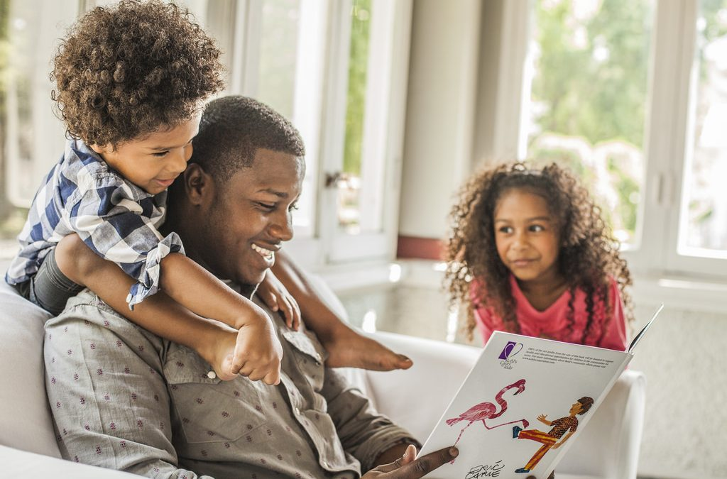 Black dad reading a book with his two kids