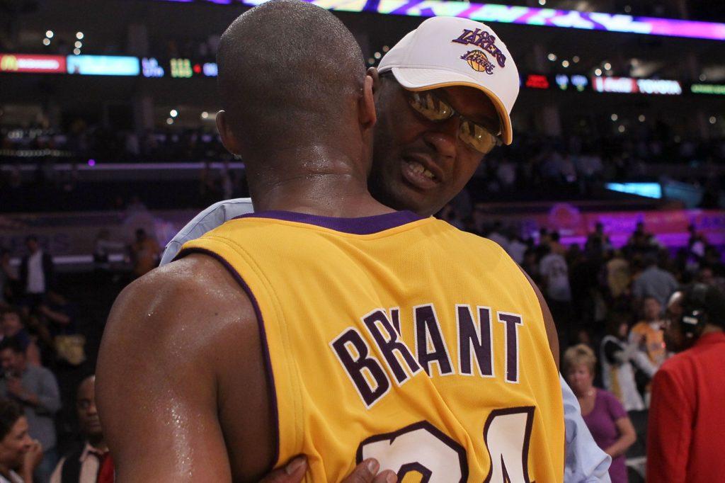 Joe Bryant hugging his son Kobe Bryant during a game