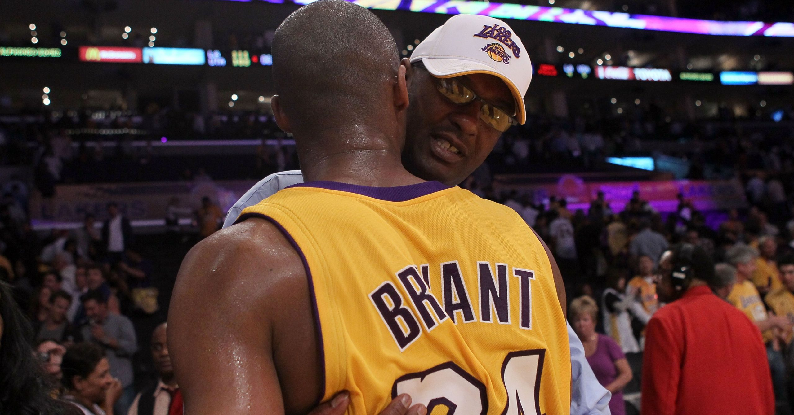 Joe Bryant hugging his son Kobe Bryant during a game