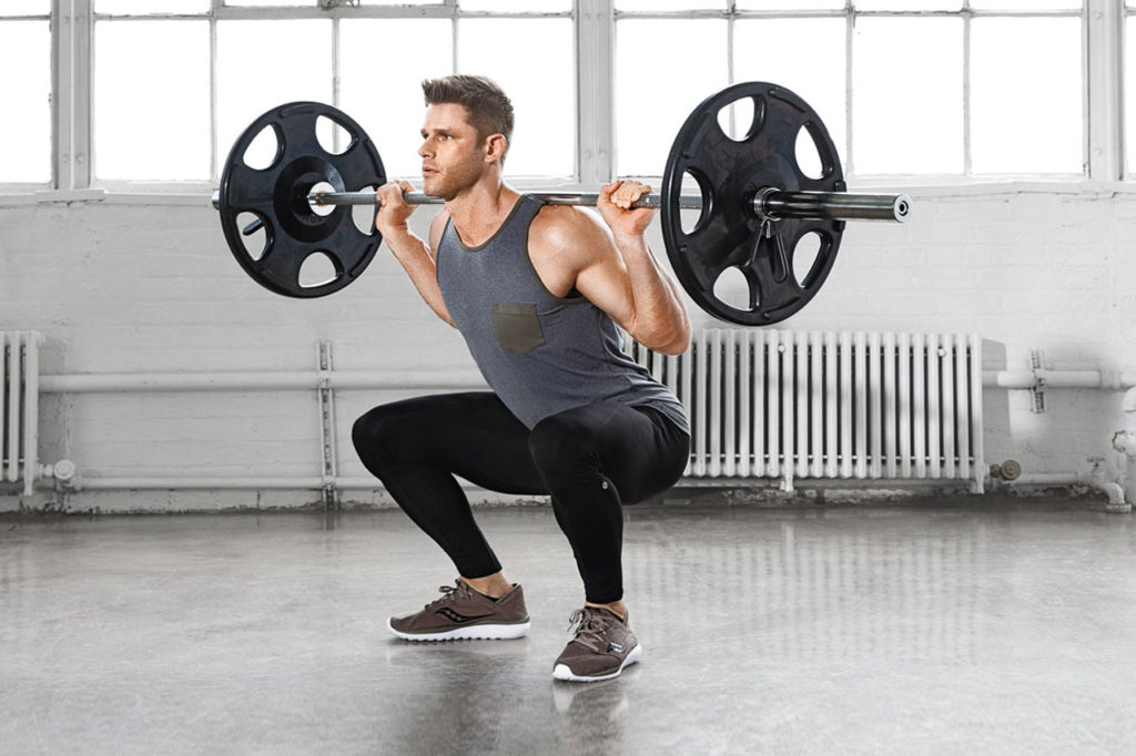 Jeremy Ethier, the founder of Built with Science, doing squats with weights