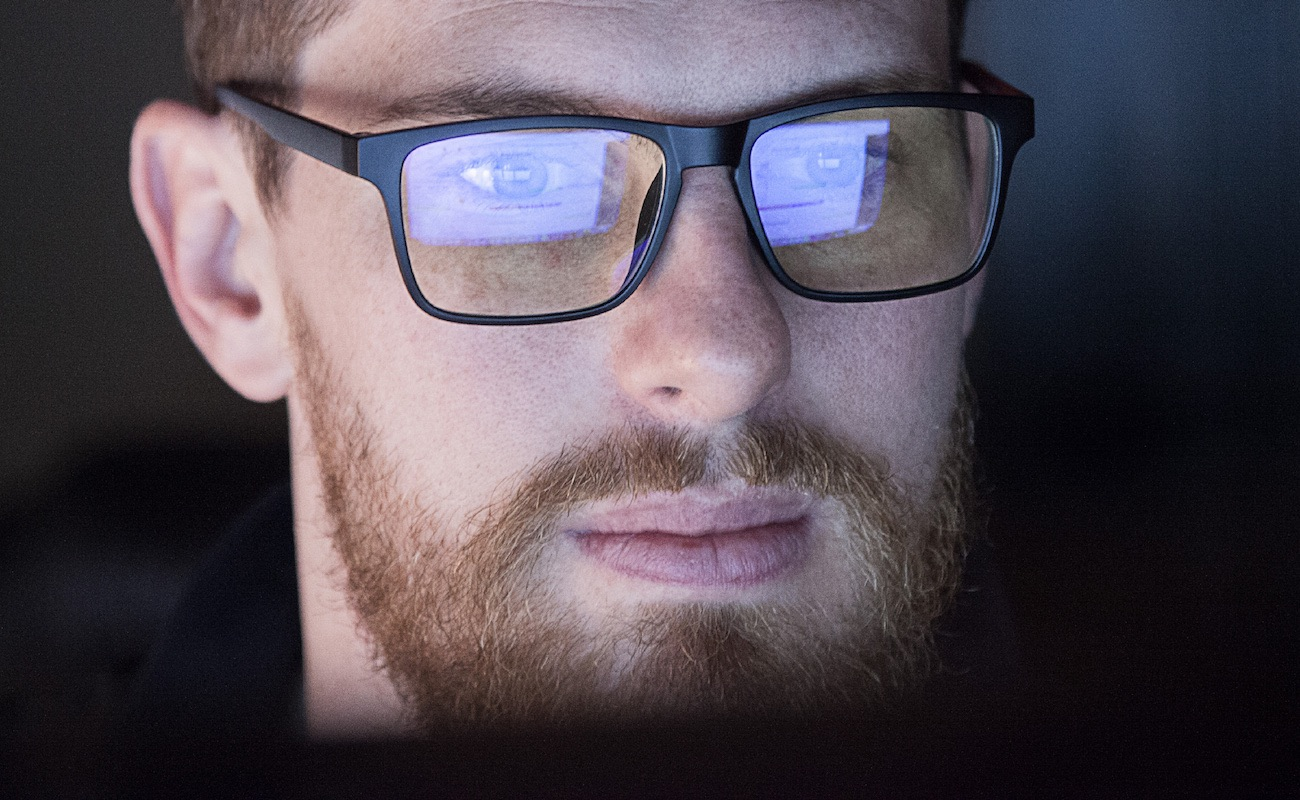 A young man wearing blue light blocking glasses