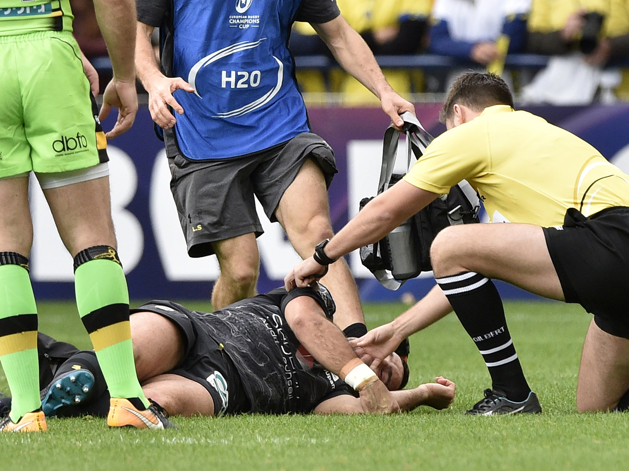 A rugby player laying on the field after an injury