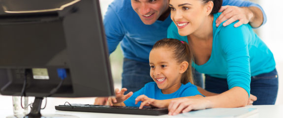 happy family using computer together at home